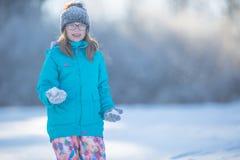 Muchacha Pre-adolescente joven feliz en la ropa caliente que juega con nieve Fotos de archivo libres de regalías