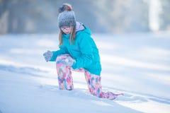 Muchacha Pre-adolescente joven feliz en la ropa caliente que juega con nieve Fotos de archivo