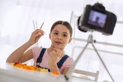 Muchacha pre-adolescente optimista que revisa gummies en su blog video Imagen de archivo libre de regalías