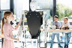 muchacha Pre-adolescente que comprueba la flexibilidad de la mano robótica Imagenes de archivo