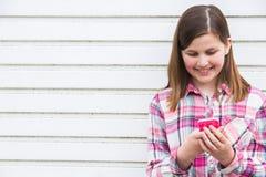 Muchacha pre adolescente que manda un SMS en el teléfono móvil en el ambiente urbano Imagenes de archivo