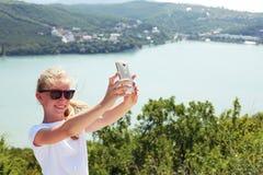 Muchacha pre adolescente que toma la foto del selfie en el top de la montaña encendido Imagen de archivo