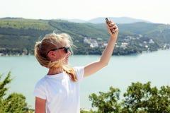 Muchacha pre adolescente que toma la foto del selfie en el top de la montaña encendido Imagen de archivo libre de regalías
