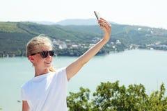 Muchacha pre adolescente que toma la foto del selfie en el top de la montaña encendido Foto de archivo libre de regalías