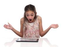Muchacha pre-adolescente sorprendida con una tableta Imágenes de archivo libres de regalías