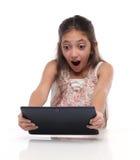 Muchacha pre-adolescente sorprendida con una tableta Fotos de archivo libres de regalías