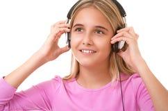 Muchacha preciosa adolescente con música que escucha de los auriculares aislada Foto de archivo libre de regalías