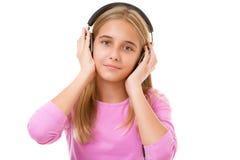 Muchacha preciosa adolescente con música que escucha de los auriculares aislada Fotografía de archivo