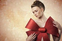 Muchacha preciosa con el arco de la Navidad Imagen de archivo
