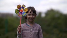 Muchacha preciosa con el juguete del molino de viento en la naturaleza que sonríe y que mira la cámara imágenes de archivo libres de regalías