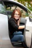 Muchacha preciosa con el teléfono celular en coche Fotos de archivo libres de regalías