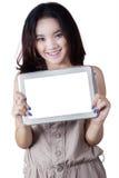 Muchacha preciosa con una pantalla en blanco de la tableta Imagenes de archivo