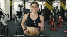 Muchacha preciosa del ajuste que corre en el fondo del gimnasio almacen de metraje de vídeo