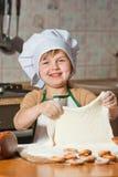 Muchacha preciosa en el sombrero de un cocinero que cocina la torta dulce Imágenes de archivo libres de regalías