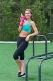 Muchacha preciosa en ropa de deportes con una botella de agua Foto de archivo libre de regalías