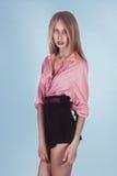 Muchacha preciosa en una camisa rosada y pantalones cortos negros Imagen de archivo