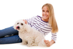 Muchacha preciosa feliz que pone en el piso con el perro maltés, aislado Fotos de archivo