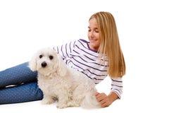 Muchacha preciosa feliz que pone en el piso con el perro maltés, aislado Fotos de archivo libres de regalías
