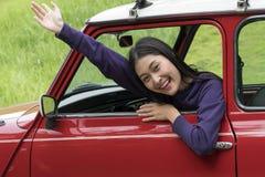 Muchacha preciosa feliz que se sienta en coche rojo Imagen de archivo libre de regalías
