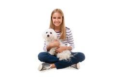 Muchacha preciosa feliz que se sienta en el piso con el perro maltés en su rodilla, aislada Imagenes de archivo