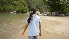 Muchacha preciosa que camina en la playa durante verano metrajes