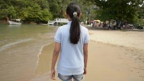 Muchacha preciosa que camina en la playa durante verano almacen de metraje de vídeo