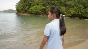 Muchacha preciosa que camina en la playa durante verano almacen de video