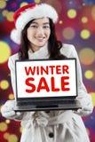 Muchacha preciosa que muestra un texto de la venta del invierno Imagenes de archivo