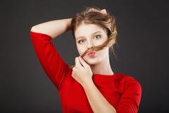 Muchacha preciosa que se divierte que muestra un bigote del pelo Imagen de archivo