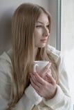 Muchacha preciosa que se sienta con una taza caliente cerca de la ventana Imagenes de archivo