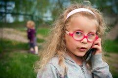 Muchacha preescolar con el teléfono Imagenes de archivo