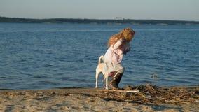 Muchacha preescolar de la muchacha que juega con un perro marr?n de Labrador en la playa Primavera o verano fr?o almacen de video