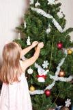 Muchacha preescolar encantadora que adorna el árbol de navidad fotografía de archivo libre de regalías