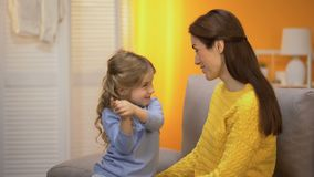 Muchacha preescolar linda que cuenta a mamá feliz las historias divertidas, riendo y abrazo almacen de video