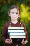 Muchacha preescolar que sostiene la pila de libros y de sonrisa Fotos de archivo