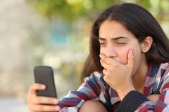 Muchacha preocupante del adolescente que mira su teléfono elegante Imágenes de archivo libres de regalías