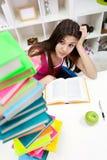 Muchacha preocupante del estudiante que mira en libros Foto de archivo libre de regalías
