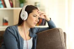Muchacha preocupante que escucha la música en casa Imágenes de archivo libres de regalías