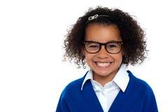 Muchacha primaria con gafas en un fondo blanco Foto de archivo libre de regalías