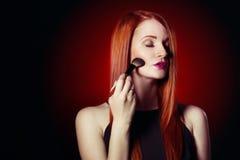 Muchacha principal roja de la belleza con el cepillo del maquillaje Imagen de archivo