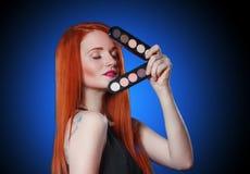 Muchacha principal roja de la belleza con las sombras de ojos del maquillaje imagen de archivo libre de regalías