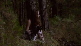 Muchacha probable que se sienta en naturaleza con su perro de lobo-mirada
