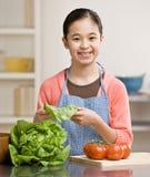 Muchacha provechosa que prepara la ensalada en cocina Imágenes de archivo libres de regalías