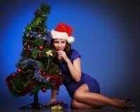 Muchacha puesta cerca del árbol de navidad Fotos de archivo libres de regalías