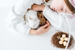 Muchacha que abraza conejos y la cesta con los huevos de Pascua en jerarquía Imágenes de archivo libres de regalías