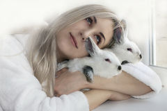 Muchacha que abraza dos conejos Imagen de archivo libre de regalías