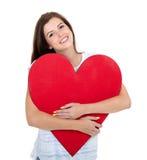Muchacha que abraza el corazón rojo Fotografía de archivo