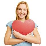 Muchacha que abraza el corazón rojo como símbolo del amor Imagenes de archivo