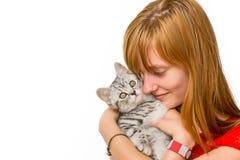 Muchacha que abraza el gato de gato atigrado de plata joven Imagen de archivo libre de regalías
