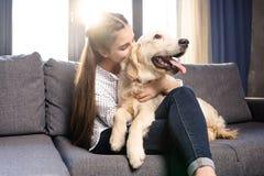 Muchacha que abraza el perro del golden retriever en el sofá en casa Fotografía de archivo